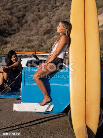 Woman relaxing on the car after a long day at the beach in California.