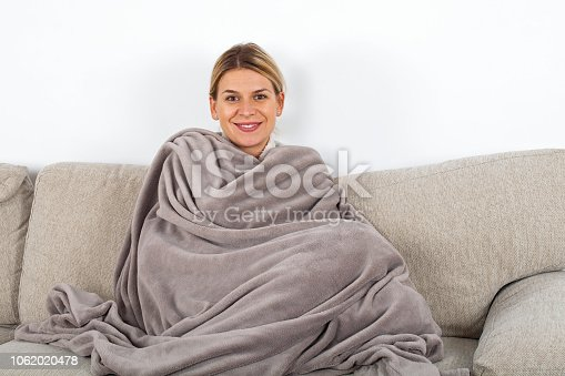 Cute blonde woman relaxing o the sofa wrapped in a soft grey blanket, white wall in the background