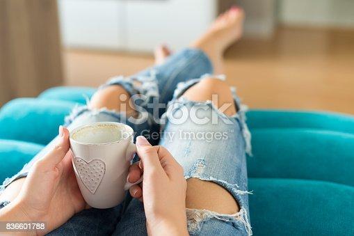 istock Woman relaxing on the sofa, watching tv and enjoying coffee 836601788