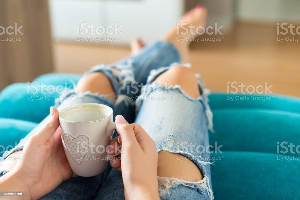 Frau auf dem Sofa entspannen, Fernsehen und Kaffeegenuss – Foto