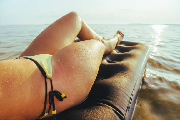 woman relaxing on water mattress at the lake - woman leg beach pov stock photos and pictures