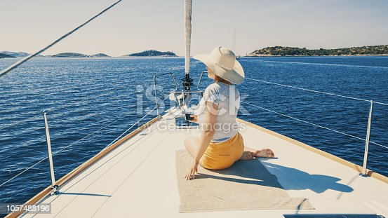 Portrait of woman relaxing on deck of sailing yacht through calm sea