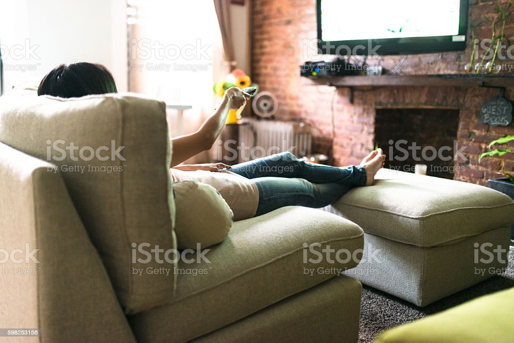 woman relaxing online on sofa reading some papers – Foto