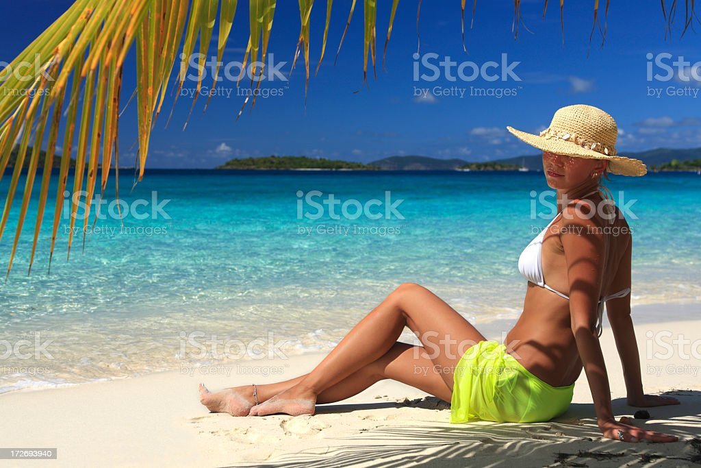 woman relaxing under a palm tree stock photo