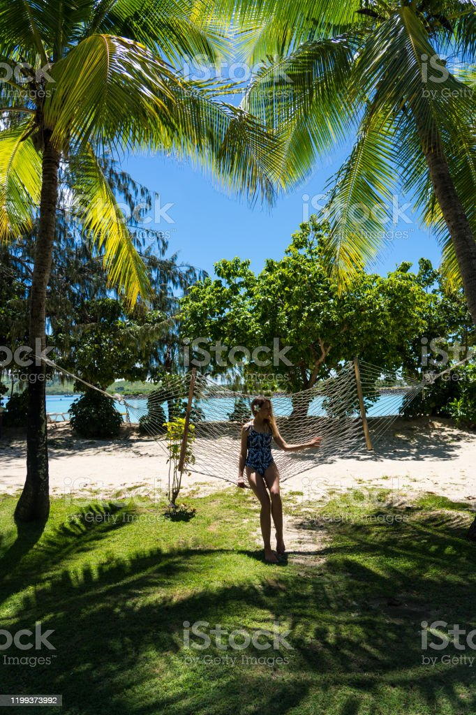 Young Woman Lying On Palm Tree High-Res Stock Photo