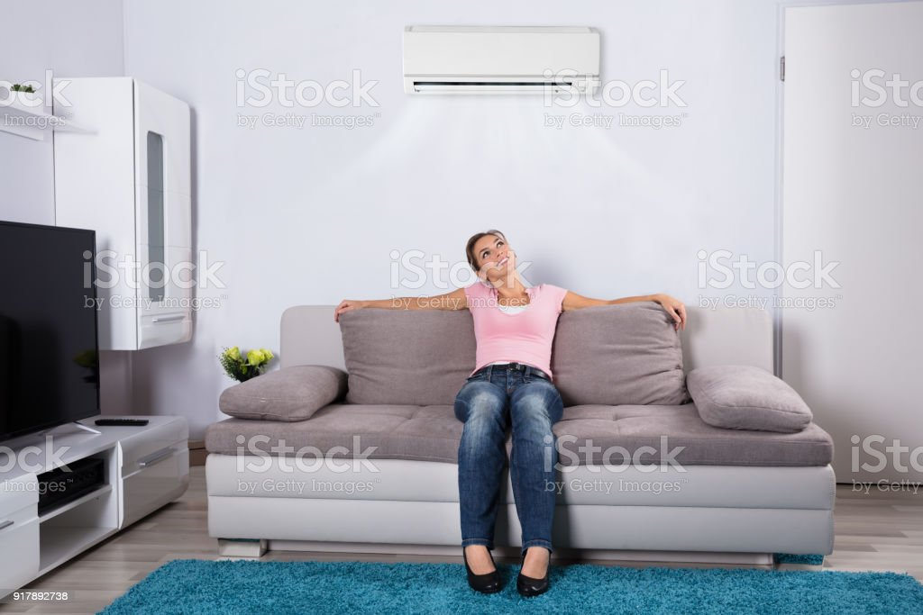 Woman Relaxing Under The Air Conditioner stock photo