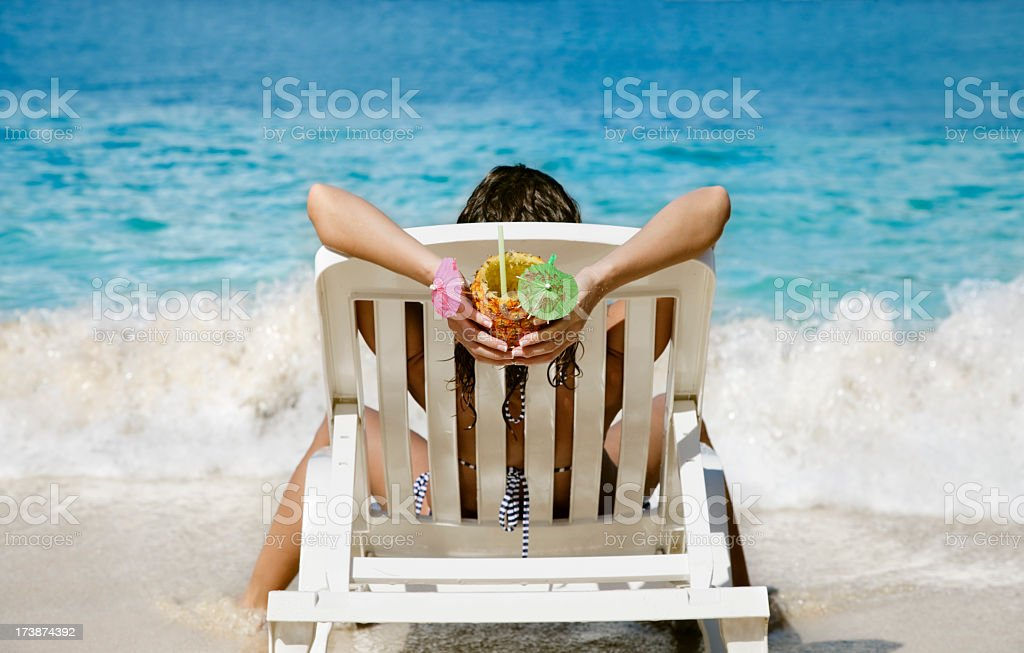 woman relaxing with a cocktail at the beach stock photo
