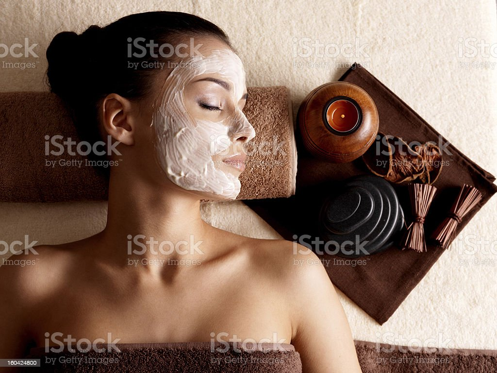 Woman relaxing with a facial mask at a beauty spa stock photo