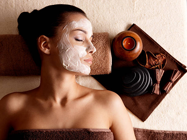 woman relaxing with a facial mask at a beauty spa - spa treatment stock photos and pictures