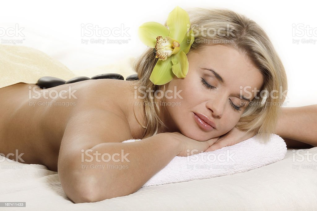 Woman relaxing with flower and hot stones stock photo