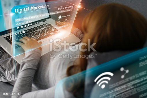 861940002 istock photo Woman relaxing with hologram modern virtual screen interface online shopping, laptop computer networking connection banking payment. Future technology and digital marketing concept. 1051617190