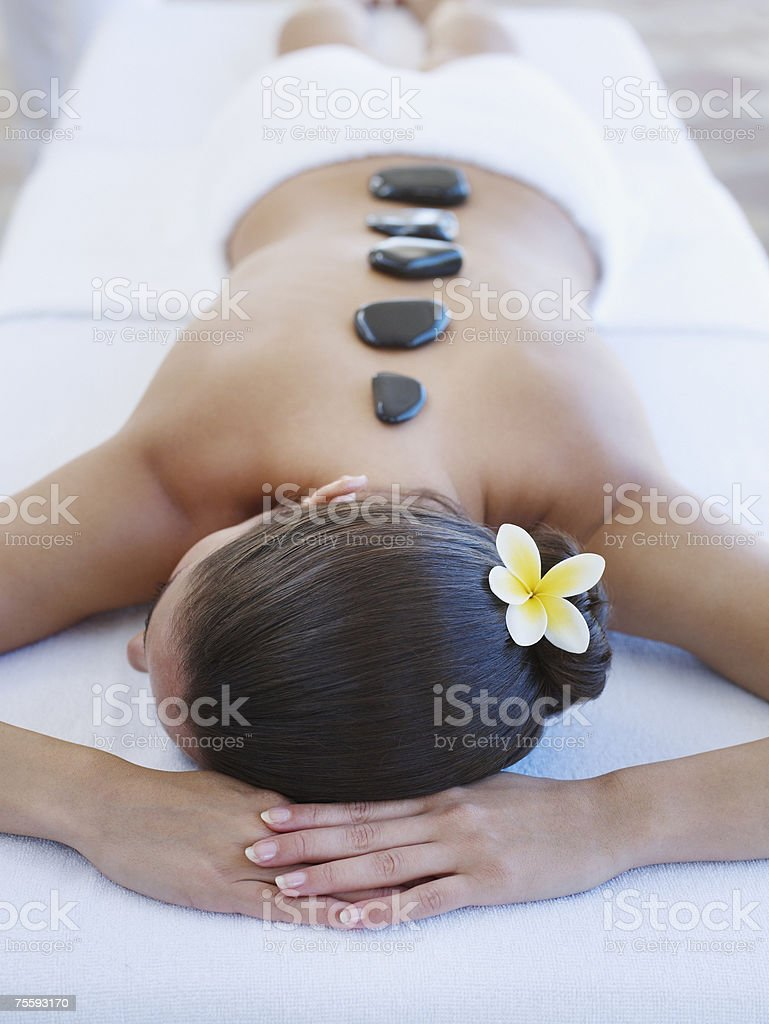 Woman relaxing with massage stones on her back stock photo