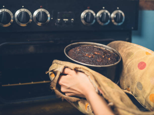 Woman removing burnt cake from oven stock photo