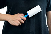 istock woman removing dog and cat hair from clothes using adhesive roller, 816759080