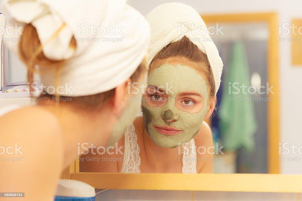 Femme suppression du visage de masque de boue argile dans la salle de bains - Photo