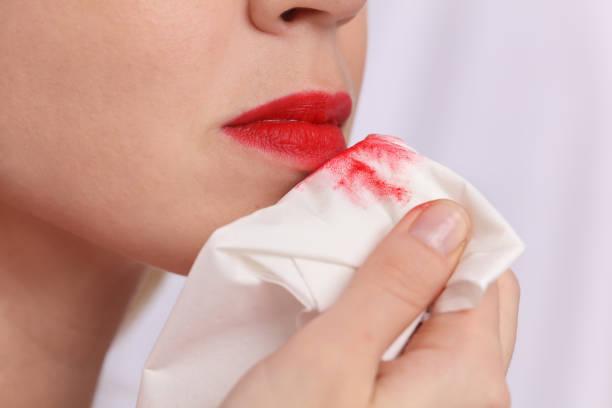 femme enlevant composent avec la lotion de nettoyage fermez vers le haut. rouge à lèvres marque sur papier blanc serviette - démaquillant photos et images de collection
