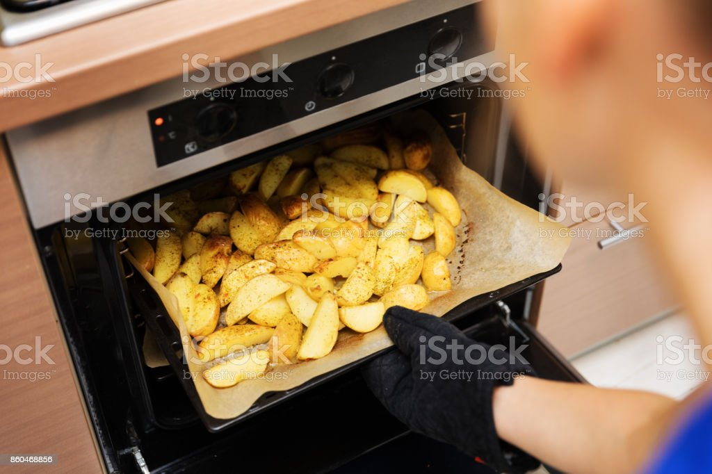 woman removing prepared potatoes tray out of oven stock photo