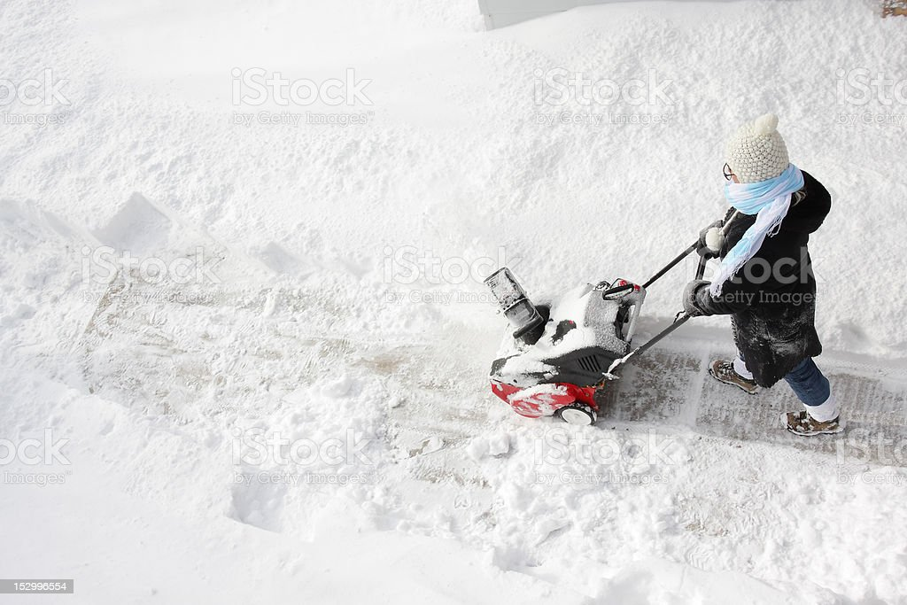 Woman removing snow after a storm royalty-free stock photo