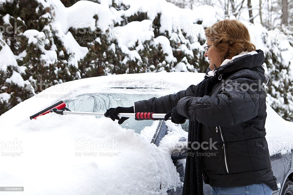 Woman removing snow from car windshield royalty-free stock photo