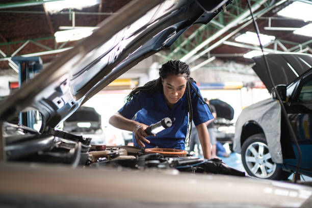 Woman repairing a car in auto repair shop Woman repairing a car in auto repair shop mechanic stock pictures, royalty-free photos & images