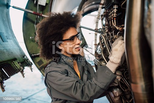 Female mechanic repairing an airplane