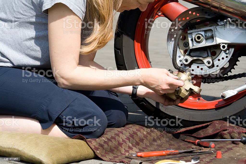 woman reparing motorbike royalty-free stock photo