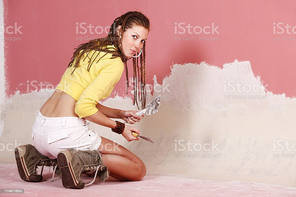 Woman reparing the wall stock photo