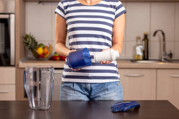 Woman replacing filter in a water pitcher stock photo