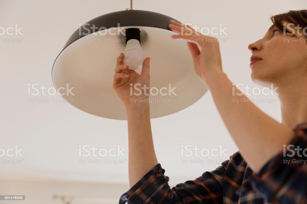 Frau Auswechseln der Glühbirne zu Hause. Energie sparen LED Lampe wechseln – Foto