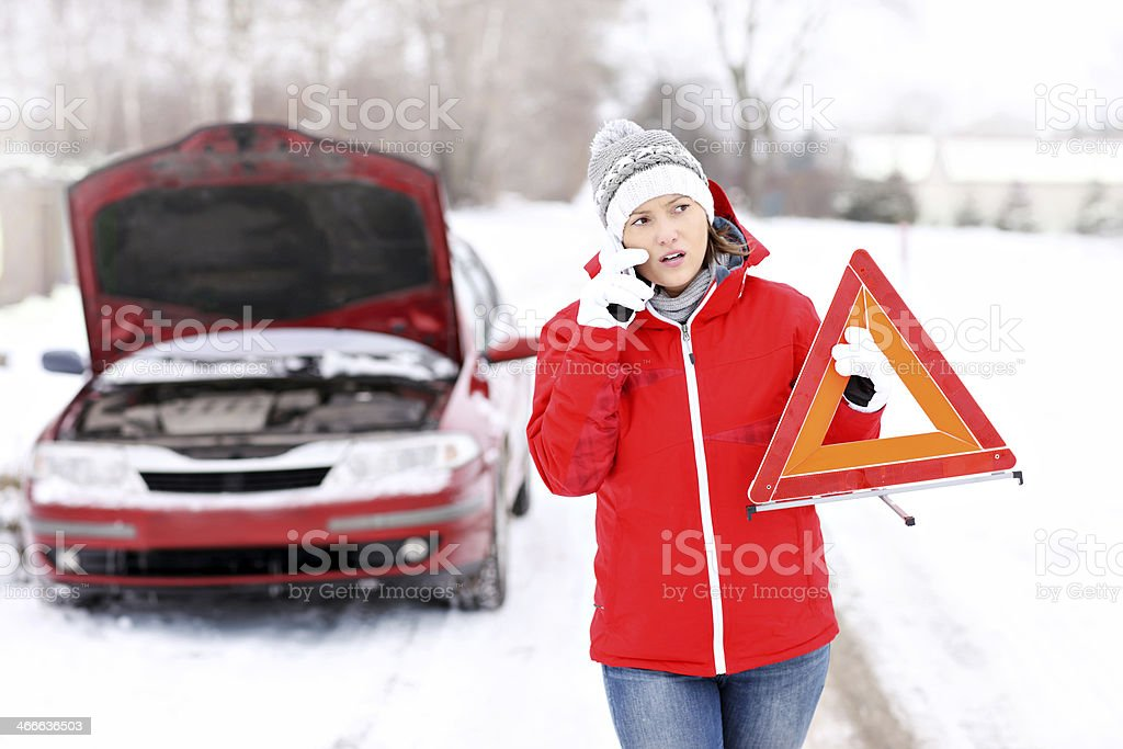 Woman reporting a car breakdown in the snow foto