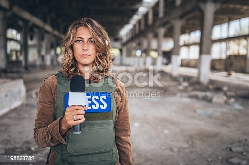 istock Woman reporting from the war zone 1198863782