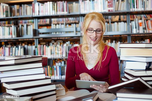 istock Woman Researching in Library on Tablet With Books 538808442