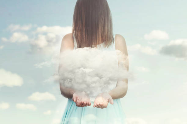 woman resembling an angel guards a small cloud in her hands stock photo