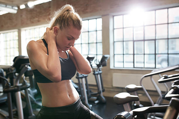 frau ruhen nach cycling-training im fitnessraum - hals übungen stock-fotos und bilder
