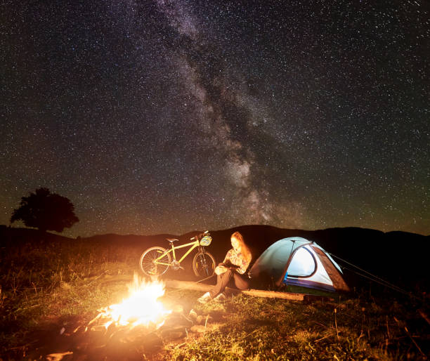 Woman resting at night camping near campfire, tourist tent, bicycle under evening sky full of stars Young woman tourist having a rest at night camping near burning campfire, illuminated tourist tent, mountain bicycle under amazing beautiful evening sky full of stars and Milky way. Astrophotography female biker resting stock pictures, royalty-free photos & images