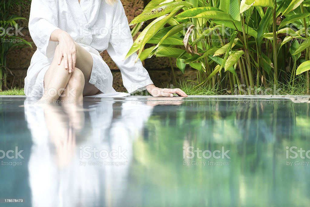 Woman resting at pool with feet in water. stock photo