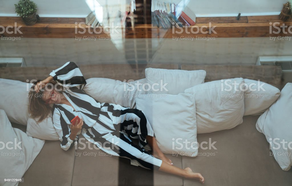Woman resting at the sofa and texting стоковое фото