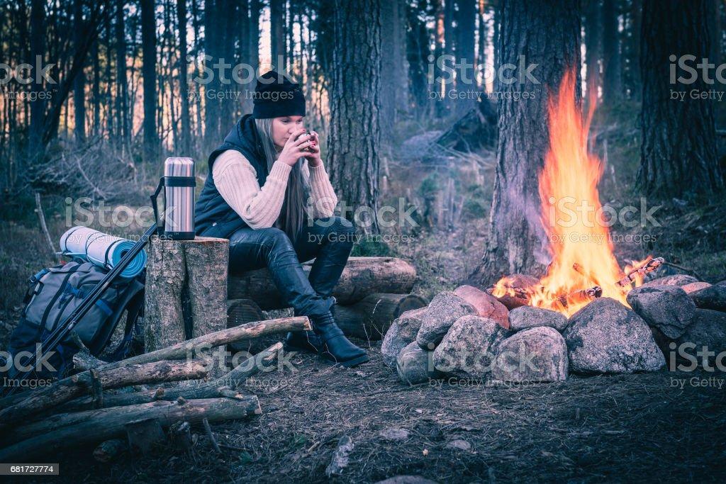 Une femme au repos par le feu de camp et de boire une boisson chaude - Photo