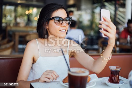 Woman resting in a cafe and making selfie with a mobile phone