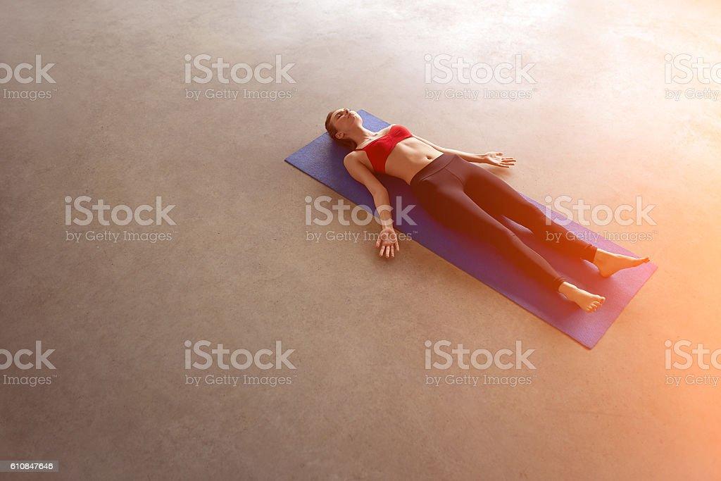 Woman resting in Shavasana during Yoga. stock photo