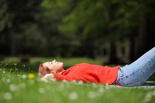 Woman resting lying on the grass in a park or forest