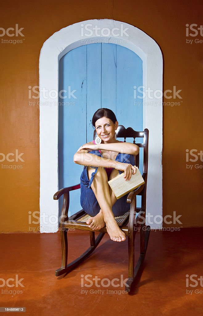 Woman resting on a rustic porch Young woman on the tropical vacation, sitting on a rocking chair and holding a book in her hand. Looking at camera and smiling. 30-34 Years Stock Photo