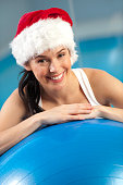 Woman resting on exercise ball with Santa hat swimming pool in background