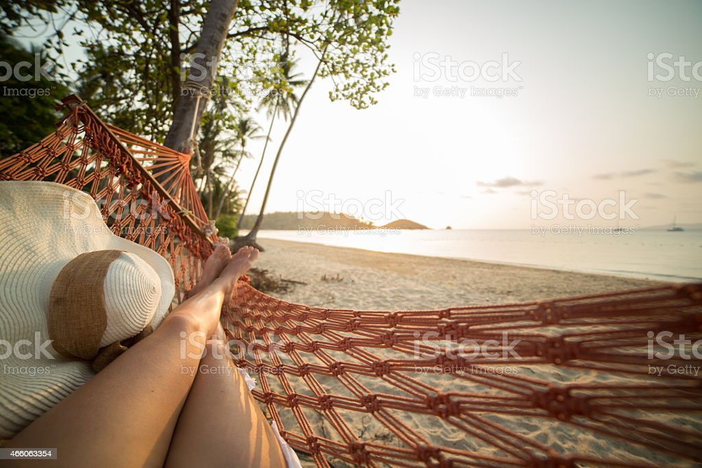 Woman resting on hammock on tropical beach Young woman on a tropical beach in Thailand lying down on a hammock relaxing. Sunset time on the Island. Shot with 5D Mark III, point of view from the woman's perspective. 2015 Stock Photo