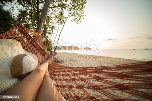 Young woman on a tropical beach in Thailand lying down on a hammock relaxing. Sunset time on the Island. Shot with 5D Mark III, point of view from the woman's perspective.