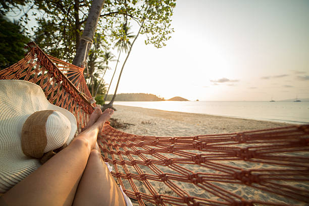 woman resting on hammock on tropical beach - hangmat stockfoto's en -beelden