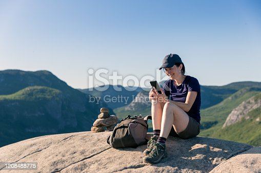 Woman Resting on Mountain Peak After Hiking at Parc National des Grands-Jardins, Quebec, Canada. She is using a mobile phone.