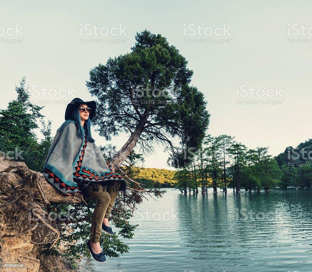 Woman resting on tree stock photo