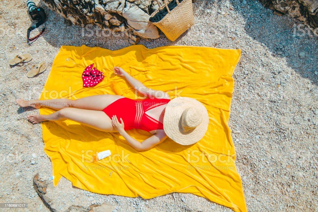 woman resting on yellow blanket sunbathing covered hat with straw...