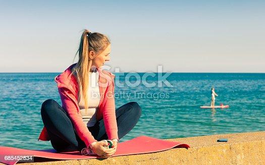 Woman resting relaxing after doing sports outdoors. Fitness girl female in sportswear on seaside takes break